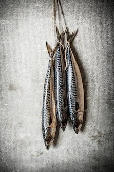 Surowe ryby wiszące na linie. na kamiennym tle.