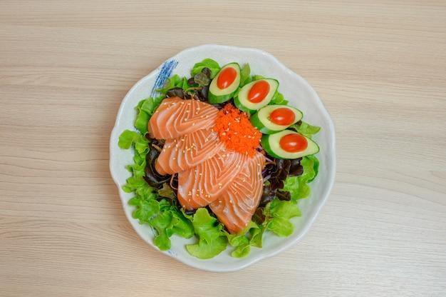 Surowe sashimi z łososia z warzywami w ceramicznej misce