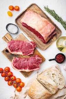Surowe składniki burger stek wołowy, z marmurkowym mięsem, na białym stole, widok z góry