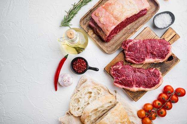 Surowe składniki burgera stek wołowy, z marmurkowym mięsem, na białym tle, widok z góry, z kopią miejsca na tekst
