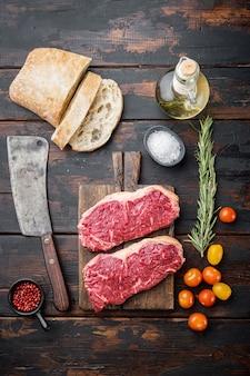 Surowe składniki burgera wołowego, z marmurkowym mięsem, na starym drewnianym stole, widok z góry