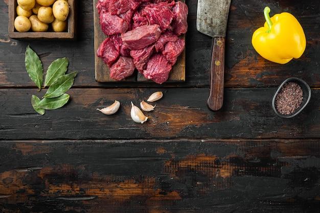 Surowe składniki gulaszu wołowego ze słodką papryką i ziemniakami, na starym ciemnym drewnianym stole, widok z góry na płasko