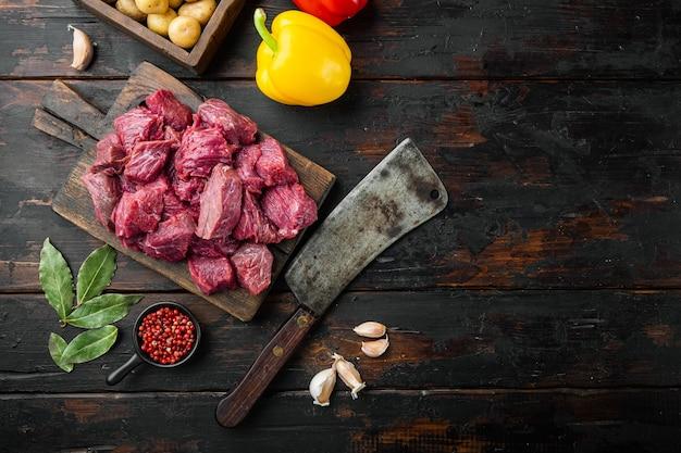 Surowe składniki gulaszu wołowego ze słodką papryką, na starym ciemnym drewnianym stole, widok z góry na płasko