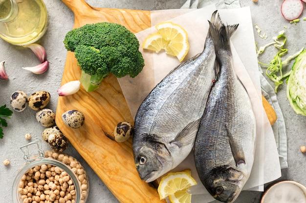 Surowe składniki kulinarne zdrowe jedzenie. świeża ryba, warzywa, zioła i rośliny strączkowe na szarym tle widok z góry