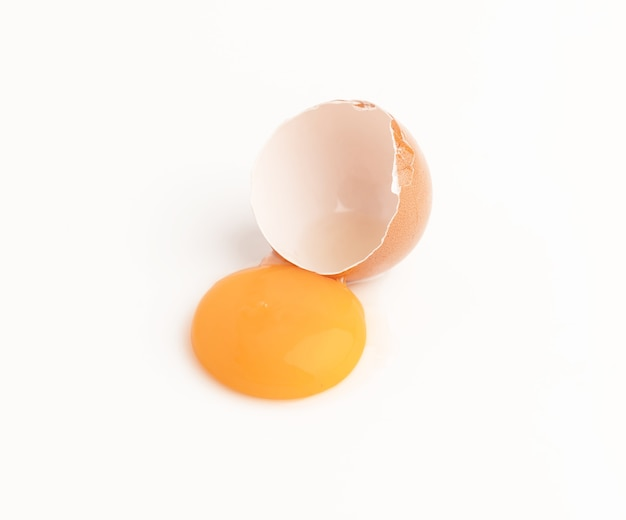 Surowe skorupki kurczaka i żółtko na białym tle
