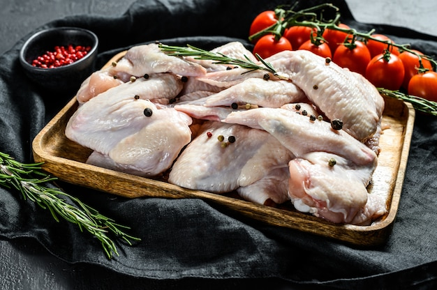 Surowe skrzydełka z indyka w drewnianej misce, składniki do gotowania rozmarynu i różowego pieprzu. ekologiczne mięso hodowlane. widok z góry.