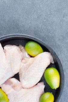 Surowe skrzydełka z kurczaka i papryczka chili na czarnym talerzu.