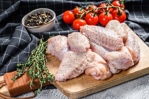 Surowe skrzydełka z kurczaka na desce do krojenia, ekologiczne mięso drobiowe