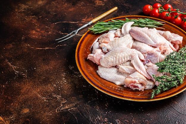Surowe skrzydełka z kurczaka pokroić w rustykalnym talerzu z tymiankiem i rozmarynem. ciemne tło. widok z góry. skopiuj miejsce.