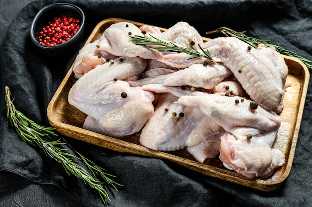 Surowe skrzydełka z kurczaka w drewnianej misce, składniki do gotowania rozmarynu i różowego pieprzu. ekologiczne mięso hodowlane. widok z góry. czarna ściana