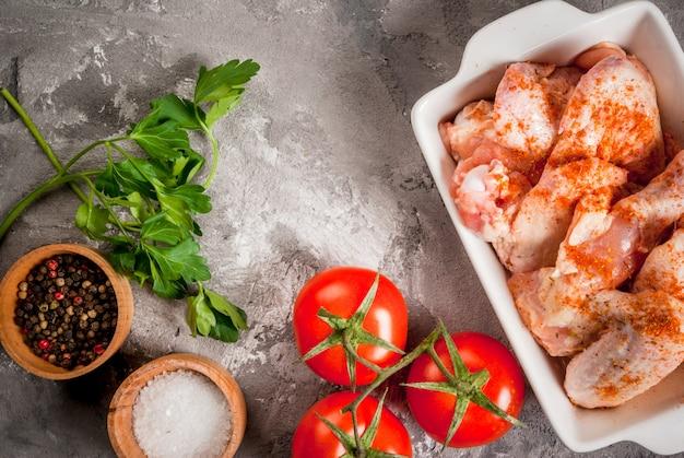 Surowe skrzydełka z kurczaka w naczyniu do pieczenia