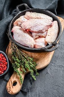 Surowe skrzydełka z kurczaka z przyprawami i ziołami na patelni