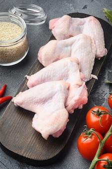 Surowe skrzydełka z kurczaka z zestawem ziół i sezamem, na drewnianej desce do krojenia, na szarym stole