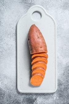 Surowe słodkie ziemniaki na desce do krojenia, ignam organiczny. warzywa rolne szare tło
