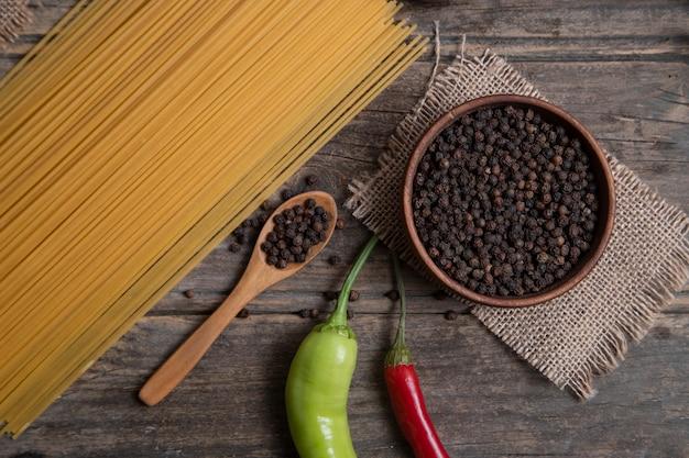 Surowe spaghetti i miska ziaren pieprzu umieszczona na drewnianej powierzchni. wysokiej jakości zdjęcie