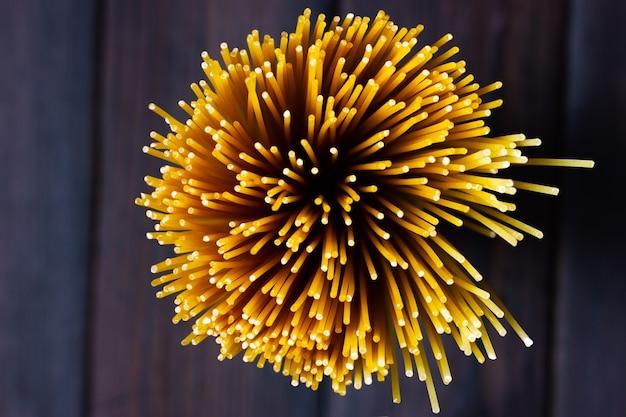 Surowe spaghetti na ciemnym tle makaron widok z góry na drewnianym ciemnym stole