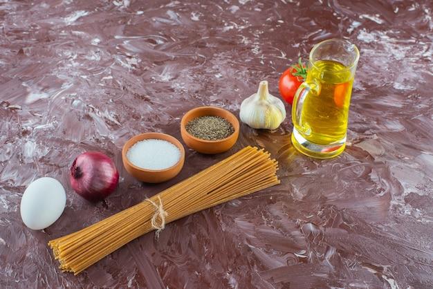 Surowe spaghetti, oliwa z oliwek i świeże warzywa na marmurowej powierzchni.
