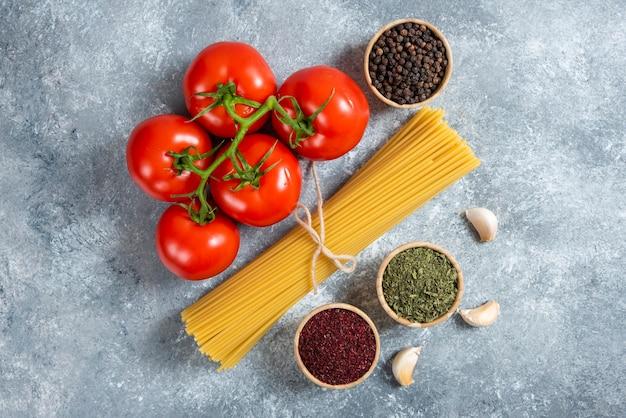 Surowe spaghetti, przyprawy i pomidory na tle marmuru.