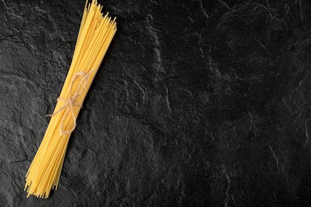 Surowe spaghetti zawiązane sznurem na czarnej powierzchni