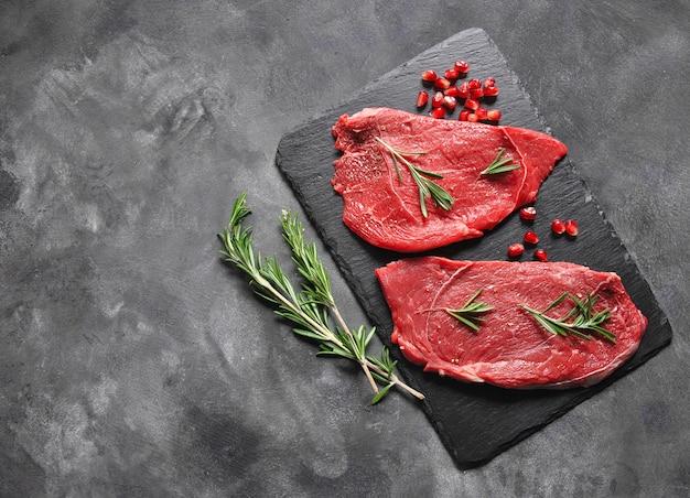 Surowe steki mięsne na czarnej powierzchni z brunchami rozmarynu i nasion granatu