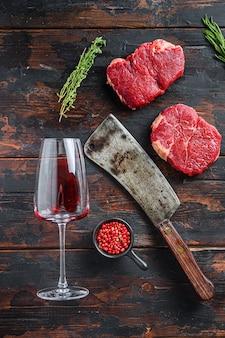 Surowe steki rumsztyk z amerykańskim tasakiem rzeźnika i dwa kieliszki czerwonego wina na ciemnym tle starego drewna, widok z góry.