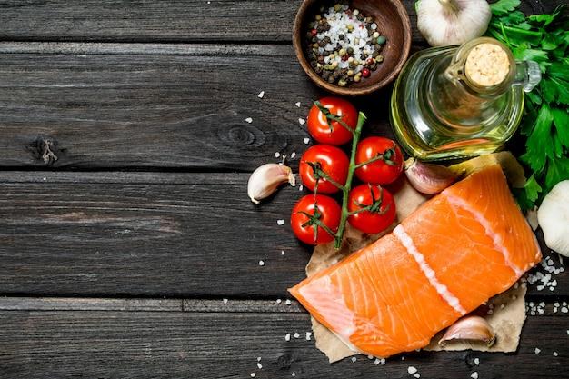 Surowe steki rybne z łososia z czosnkiem i pomidorami. na drewnianym tle.