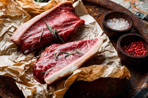 Surowe steki wołowe marmurkowe i przyprawy do ich przygotowania na starym drewnianym tle. surowe mięso wołowe na stole w kuchni. zdjęcie wysokiej jakości