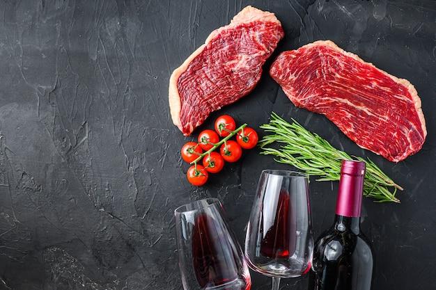 Surowe steki wołowe picanha z przyprawami i ziołami w pobliżu butelki i kieliszek czerwonego wina, na czarnym tle z teksturą widok z góry z miejsca na tekst.