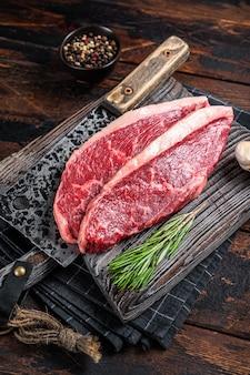 Surowe steki wołowe z polędwicy wołowej na desce rzeźnika z tasakiem do mięsa. ciemne drewniane tło. widok z góry.