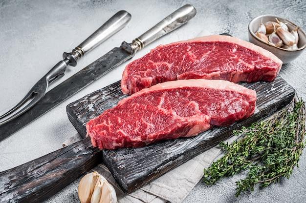 Surowe steki wołowe zad na desce z nożem do mięsa i widelcem. białe tło. widok z góry.