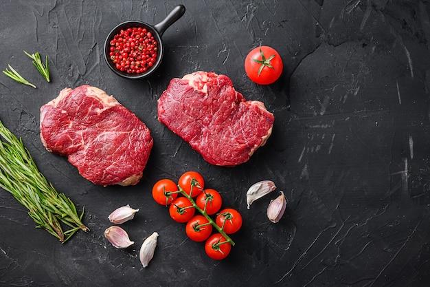 Surowe steki z ekologicznej wołowiny z kawałkami mięsa wołowego z rozmarynem, czosnkiem i przyprawami na czarnym tle z teksturą, widok z góry na tekst.