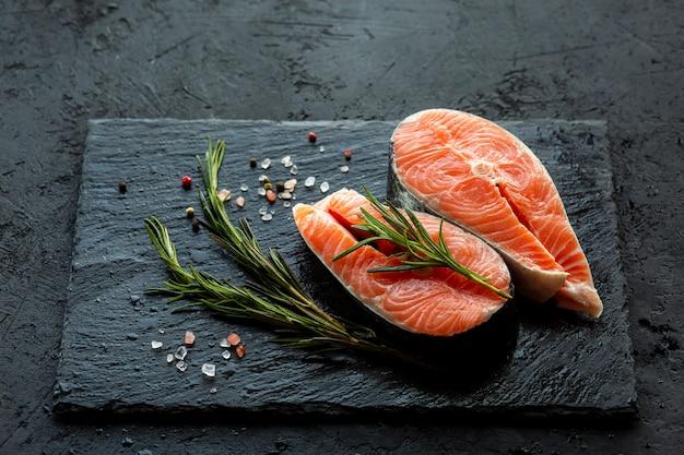 Surowe steki z łososia i składniki na desce. świeża czerwona ryba z rozmarynem, solą i pieprzem. stek z ryb z przyprawami na czarnej powierzchni. świeże kawałki ryb. miejsce na copywriting
