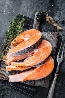 Surowe steki z łososia lub pstrąga, ryby przygotowane do gotowania na desce. czarne tło. widok z góry.
