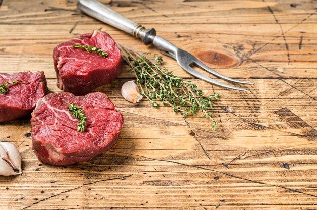 Surowe steki z polędwicy mignon, polędwica wołowa na drewnianym stole rzeźnika z widelcem do mięsa. drewniane tła. widok z góry. skopiuj miejsce.