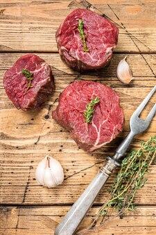 Surowe steki z polędwicy mignon, polędwica wołowa na drewnianym stole rzeźnika z widelcem do mięsa. drewniane tła. widok z góry.