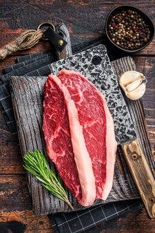 Surowe steki z polędwicy wołowej na desce rzeźnika z tasakiem do mięsa. tło ciemne drewno. widok z góry.