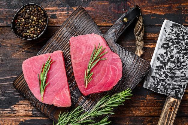 Surowe steki z tuńczyka na drewnianej desce do krojenia z tasakiem. ciemne drewniane tło. widok z góry.