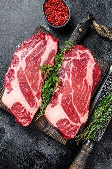 Surowe steki z wołowiny premium na desce do krojenia. czarne tło. widok z góry.