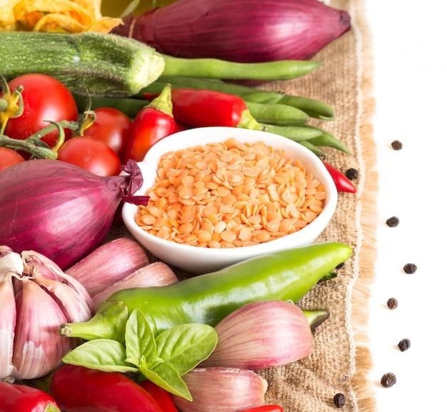Surowe suche czerwone soczewicy w pucharze i warzywach na burlap odizolowywają na bielu zakończeniu up