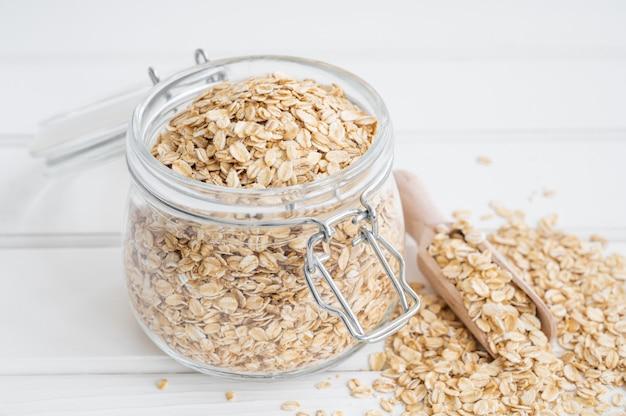 Surowe suche płatki owsiane w szklanym słoju na białym tle drewnianych. zdrowe jedzenie. skopiuj miejsce.
