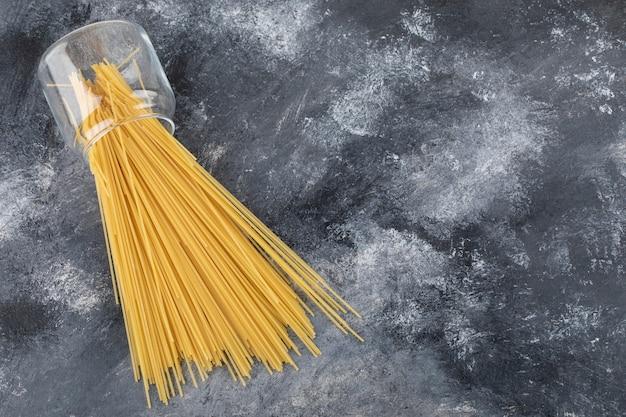 Surowe suche spaghetti w szklanym słoju na marmurowym stole.