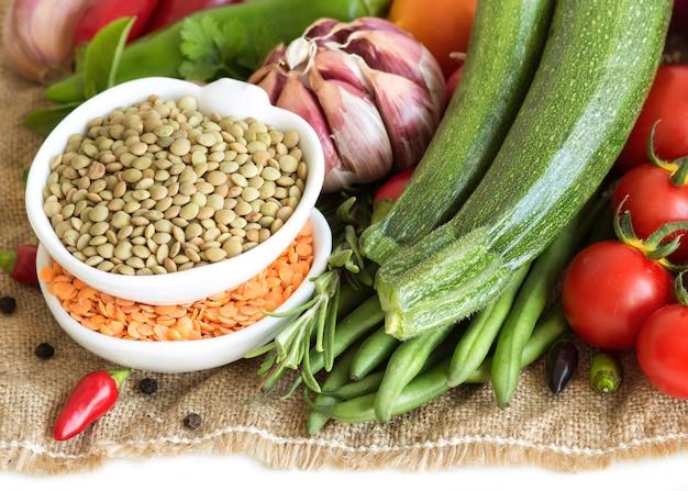 Surowe suche zielone i czerwone soczewicy w pucharach i warzywach na burlap odizolowywają na bielu zakończeniu up