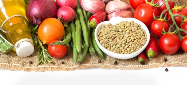 Surowe suche zielone soczewicy w pucharze i warzywach na burlap odizolowywają na bielu zakończeniu up