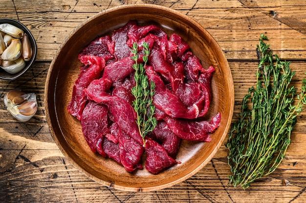 Surowe surowe mięso wołowe pokrojone w paski ze świeżymi ziołami na stroganow wołowy. drewniane tła. widok z góry.