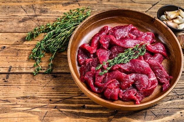 Surowe surowe mięso wołowe pokrojone w paski ze świeżymi ziołami na stroganow wołowy. drewniany stół. widok z góry.