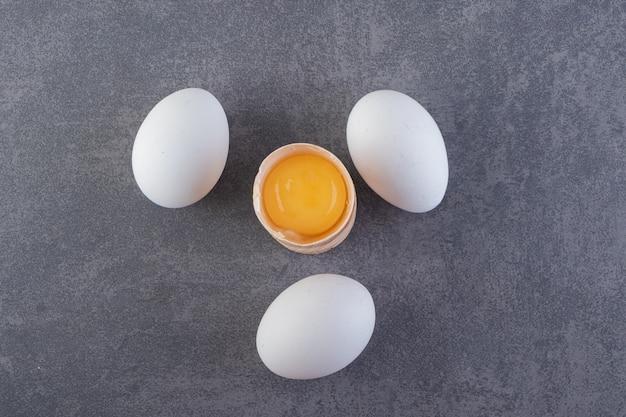 Surowe, świeże, białe jaja kurze umieszczone na kamiennej powierzchni.