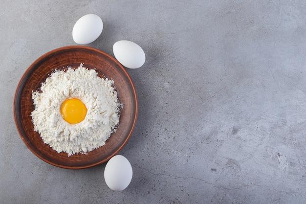 Surowe, świeże jaja kurze umieszczone na kamiennej powierzchni.