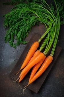 Surowe świeże marchewki na ciemnym stole. selektywna ostrość. widok z góry. skopiuj miejsce. koncepcja wegetariańska.