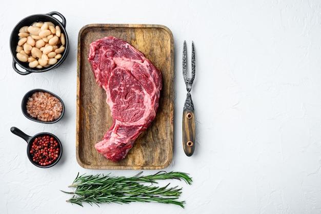 Surowe świeże mięso antrykot ribeye z mięsa black angus prime z zestawem składników, na białym kamieniu