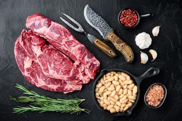 Surowe świeże mięso antrykot ribeye z mięsa black angus prime z zestawem składników, na czarnym kamieniu